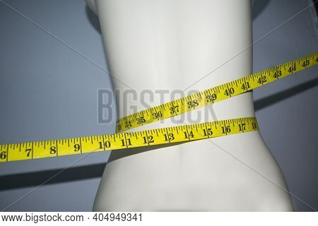 Yellow Tape Measure On The Slim Waist Of The Mannequin. The Concept Of A Weight Control Diet And Sli