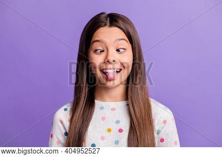 Photo Portrait Of Goofy Child Showing Tongue Looking At Nose Isolated On Vivid Violet Colored Backgr