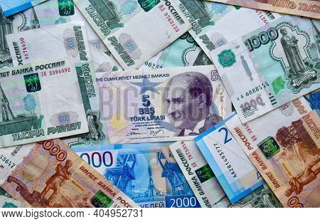 Turkish Lira Banknotes On Top Of Russian National Currency, Top View Of Mixed Rouble Banknotes. Russ