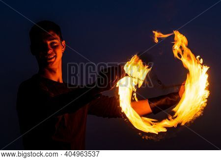 Game Of Light And Dark. Fire Spinner At Night. Happy Male Spinner Spin Burning Poi.