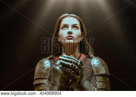 Medieval knight woman in armor prays, blessing before the battle.