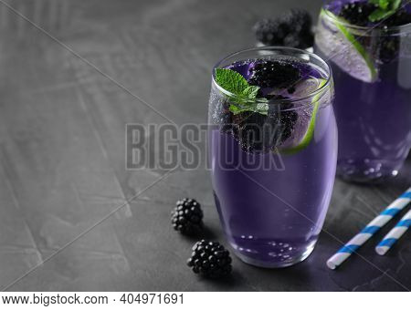 Delicious Blackberry Lemonade Made With Soda Water On Grey Table. Space For Text