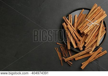 Aromatic Cinnamon Sticks On Black Table, Flat Lay. Space For Text