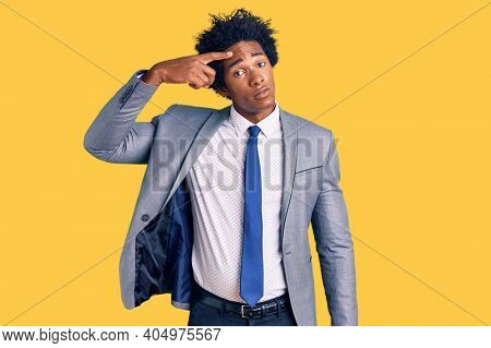 Handsome african american man with afro hair wearing business jacket pointing unhappy to pimple on forehead, ugly infection of blackhead. acne and skin problem