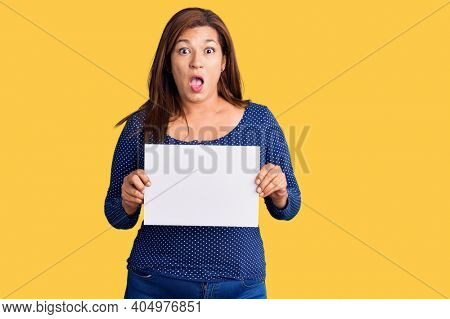 Middle age latin woman holding paper banner with blank space scared and amazed with open mouth for surprise, disbelief face