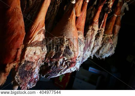 Smoked Legs Of Ham In Smokehouse. Whole Ham Hanging From The Ceiling In Farm. Healing And Drying Of