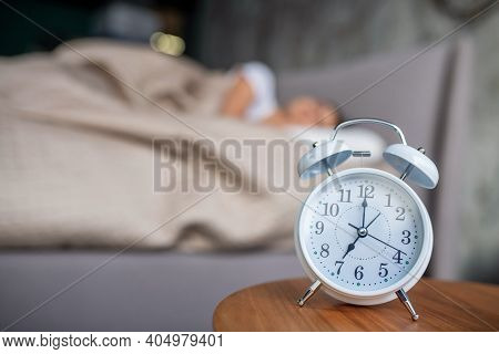 White Mechanic Alarm Cloch Standing Near The Bed