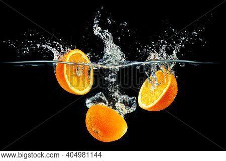 Fresh Orange Slices With Water Splashes Against A Black Background