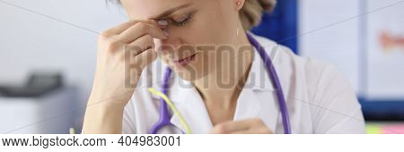 Tired Doctor With Glasses In Hand Holding His Eyes In Clinic. Emotional Burnout Of Medical Workers I
