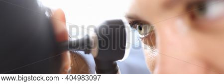 Doctors Holding Otoscope Near Patients Ear In Clinic Close-up. Diagnosis Of Otitis Media Concept