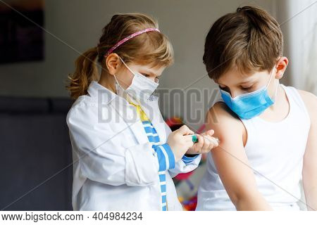 Little Girl Makes Injection To Brother, School Kid Boy. Children, Siblings With Medical Mask Playing