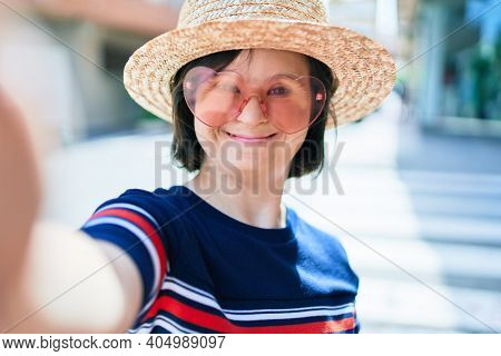 Beautiful brunette woman with down syndrome at the town on a sunny day wearing fashion heart shaped sunglasses and summer hat taking a selfie picture