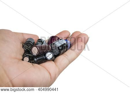 Electrolytic Capacitors Group In A Hand On White Background With Copy Space