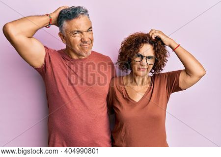 Beautiful middle age couple together wearing casual clothes confuse and wondering about question. uncertain with doubt, thinking with hand on head. pensive concept.