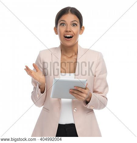 portrait of enthusiastic young woman in pink jacket holding pad, opening mouth and making a surprised face on white background in studio