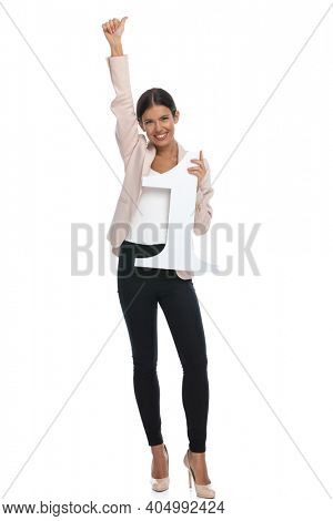 enthusiastic young businesswoman in pink jacket holding arms in the air and celebrating, holding number one sign and smiling on white background in studio, full body