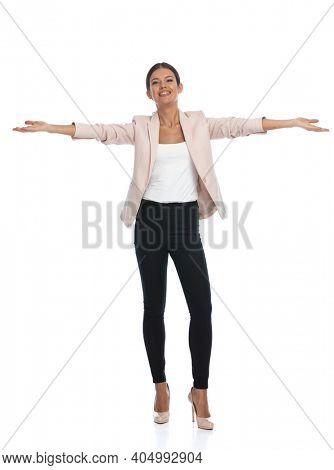 excited young woman in pink jacket smiling, enthusiastically opening arms and presenting, standing isolated on white background in studio, full body