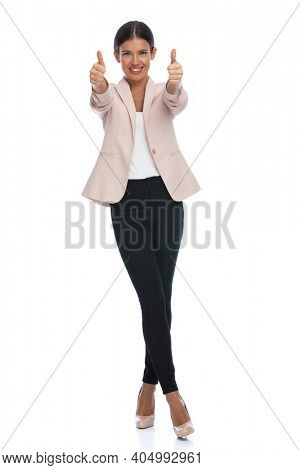 enthusiastic young woman wearing pink jacket on white background, making thumbs up gesture and smiling in studio, full body