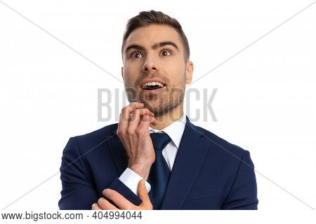 portrait of captivated businessman in navy blue suit looking up on white background, admiring, opening mouth and smiling in studio