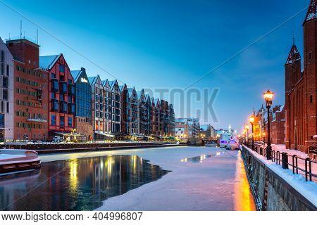 Granaries island over Motlawa river in snowy night, Gdansk. Poland