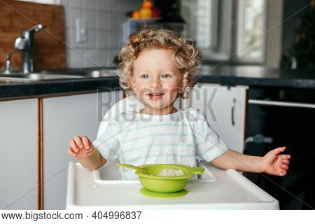 Cute Adorable Caucasian Curly Kid Boy Sitting In High Chair Eating Cereal Puree With Spoon. Healthy