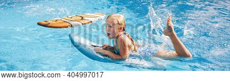 Cute Adorable Red-haired Girl With Freckles Swimming In Pool On Swim Board. Kid Child Enjoying Havin