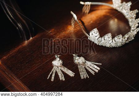 Wedding Crown For The Bride And Earrings Lie On The Trellis