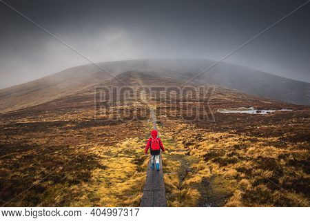 Boy In A Red Jacket, Hiking On Wooden Path Leading Through The Wicklow Mountains, Djouce Pek Ireland