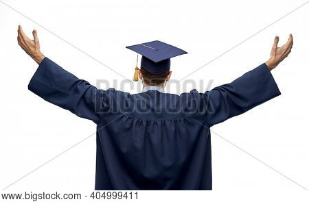 education, graduation and people concept - happy male graduate student in mortar board and bachelor gown celebrating success over white background from back