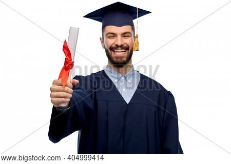 education, graduation and people concept - happy smiling male graduate student in mortar board and bachelor gown with diploma over grey background