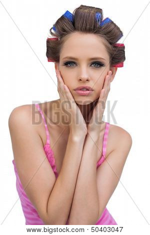 Retro styled model in hair curlers posing on white background