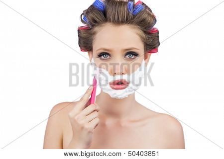 Young woman in hair curlers posing with razor on white background