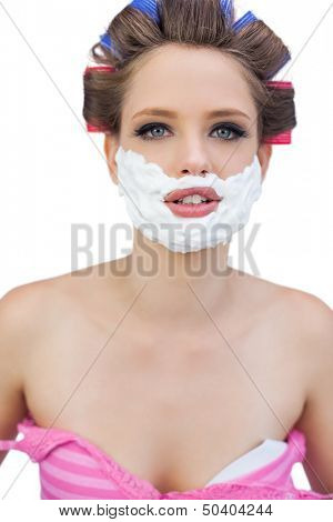 Young model in hair curlers with shaving foam posing on white background