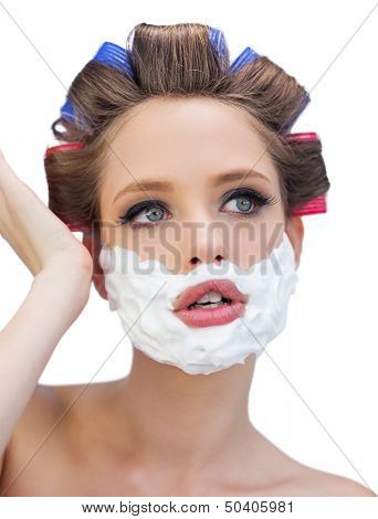 Thoughtful model in hair curlers with shaving foam posing on white background