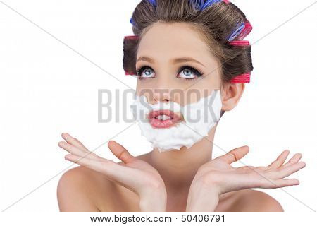 Pensive woman posing with shaving foam on face on white background