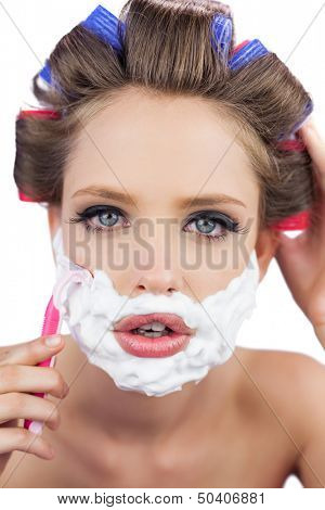 Model in hair curlers posing with shaving foam and razor in close up on white background