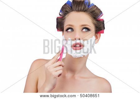 Thoughtful woman in hair curlers posing with razor on white background