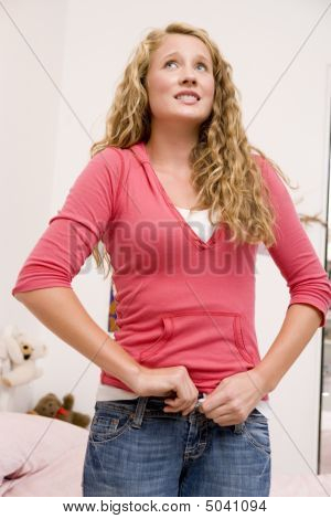 Teenage Girl Trying To Zip Up Her Denim Jeans