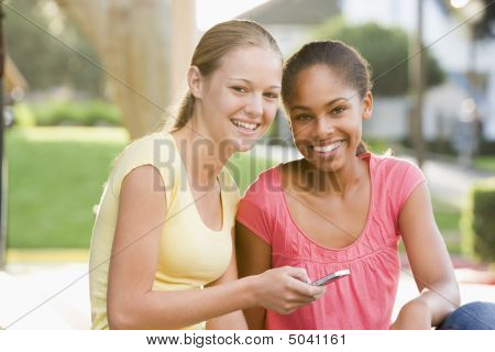 Teenage Girls Sitting Outside Playing With Mobile Phone