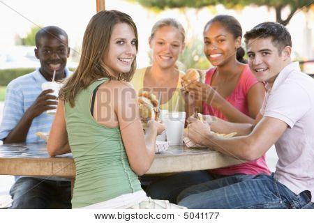 集团的青少年坐在户外吃快餐
