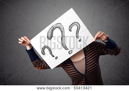 Young woman holding a paper with drawed question marks on it in front of her head