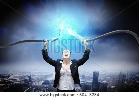 Image of businesswoman holding electrical cable above head