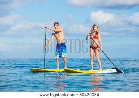 Attractive Couple Stand Up Paddling in Hawaii