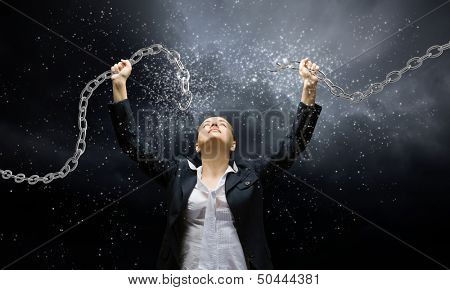 Image of businesswoman in anger breaking metal chain poster