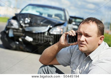 Adult upset driver man discussing on mobile phone in front of automobile crash car collision accident in city road