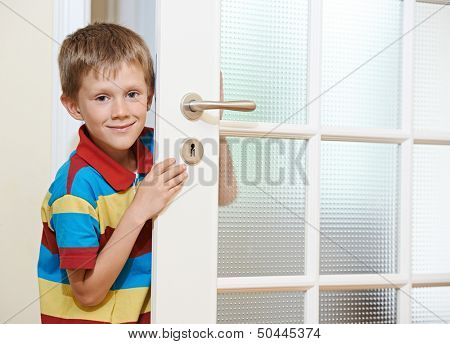 Little smiling boy opening the white door at home