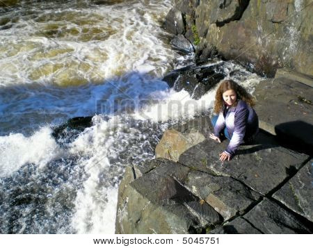 Woman On The Grey Rocks Near The Waterfall