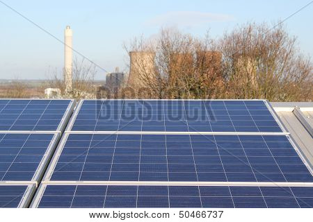 Solar PV Installation in foreground with traditional power station in background - contrasting the two technologies poster
