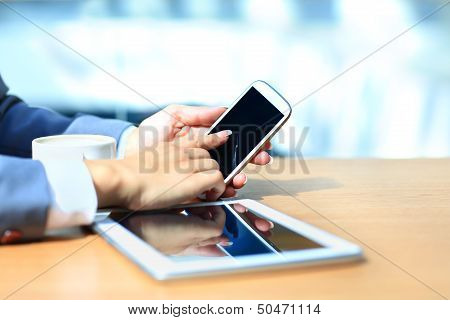 Businessman using digital tablet computer with modern mobile phone.