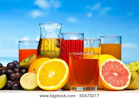 Composition with glasses of different juice, fruits and pitcher